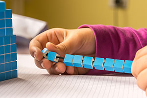 child using maths blocks on a string